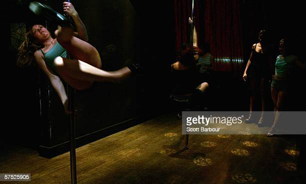 Women perform pole tricks during a Polepeople pole dancing class May 3 2006 in London England Since celebrities hailed pole dancing as the latest...