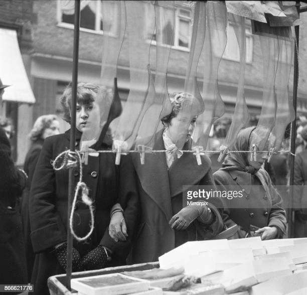 Women peruse the silk and nylon stocking on a market stall at an unnamed street market in the East End of London 11th January 1955