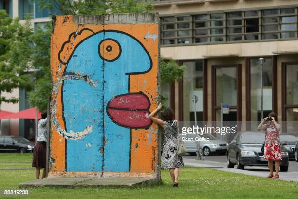 Women photograph one another at a stillstanding piece of the former Berlin Wall at Leipziger Platz on July 6 2009 in Berlin Germany The Berlin Wall...