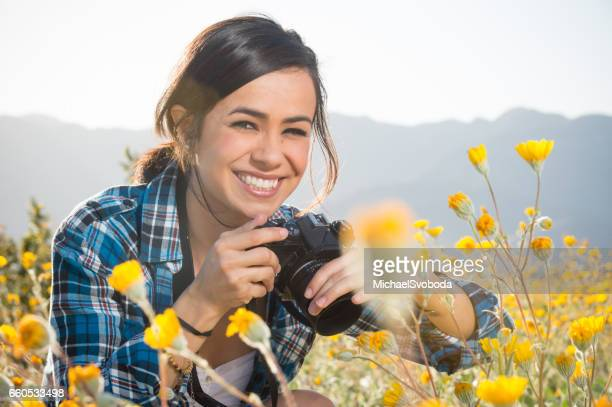women photographer in the wild flowers - photography themes stock pictures, royalty-free photos & images