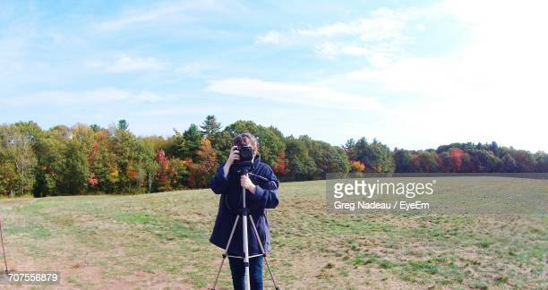 Women Photographing Through Camera On Tripod At Field Against Sky