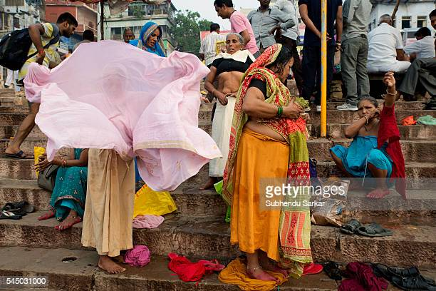 Women pilgrims change clothes on the ghats after bathing in the waters of the river Ganges in Varanasi Varanasi is a holy town for the Hindus where...