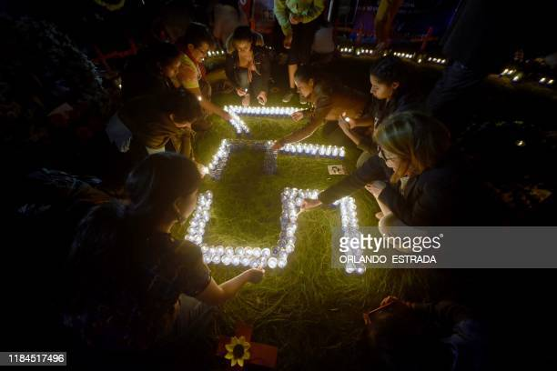 Women place candles during a vigil in memory of a murdered women before the International Day of No Violence Against Women at Constitution Square in...