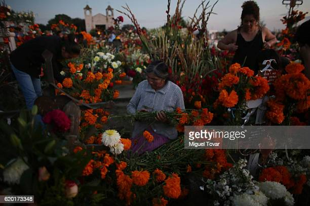 Women place cempasuchil flowers on a relative grave during during the Day of the Dead celebration known in spanish as Dia de los Muertos on November...