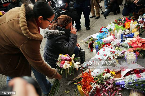 Women place flowers at a memorial to the two New York Police Department officers that were shot and killed nearby December 21 2014 in the Bedford...
