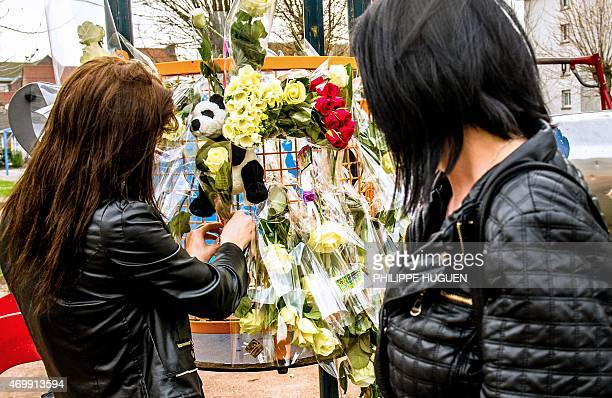 Women place flowers on a slide at a playground on April 16 2015 in the neighborhood where Chloe a nineyearold girl who was snatched on April 15 in...