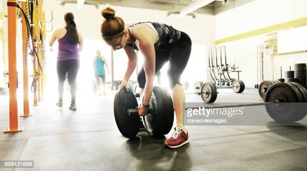 Women placing weight on barbell.