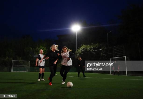 women play a competitive game of football - menopossibilities stock pictures, royalty-free photos & images