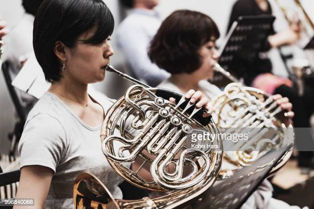 Women playing a horn at concert hall in rehearsal