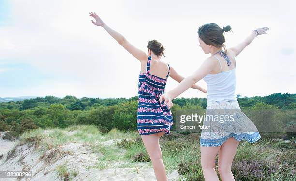 women playing airplane on beach - following stock pictures, royalty-free photos & images