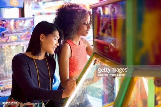 Women playing arcade game at fun fair