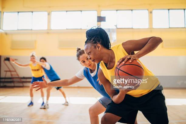 women playing basketball indoors - women's basketball stock pictures, royalty-free photos & images