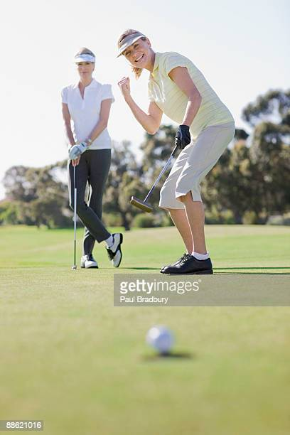 damen golf spielen - einlochen golf stock-fotos und bilder