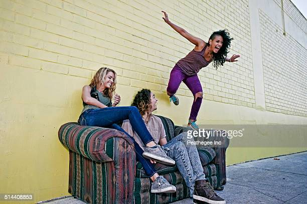 Women playing on sofa on city street