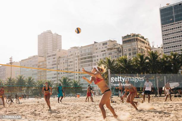 women playing professional beach volleyball at copacabana beach in rio de janeiro - beach volleyball stock pictures, royalty-free photos & images