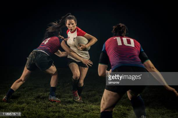 women playing rugby on field - rugby stock pictures, royalty-free photos & images