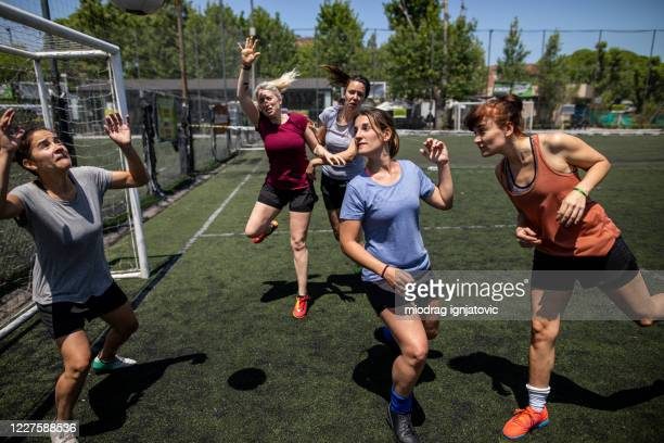 women playing soccer on soccer field during beautiful summer day - corner kick stock pictures, royalty-free photos & images