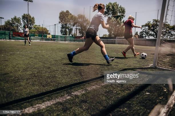 mujeres jugando al fútbol - fútbol femenino fotografías e imágenes de stock