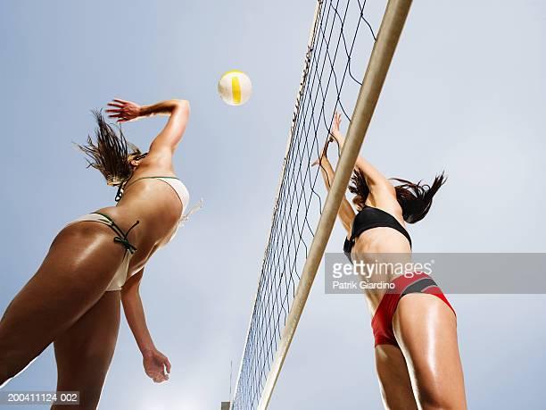women playing volleyball, low angle view - vóleibol de playa fotografías e imágenes de stock