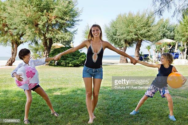 Women playing with 2 children by the sea