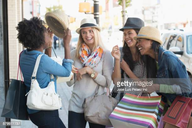 women playing with hats on city sidewalk - fedora stock pictures, royalty-free photos & images