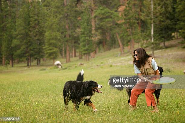 Women playing with her dog in the mountains.