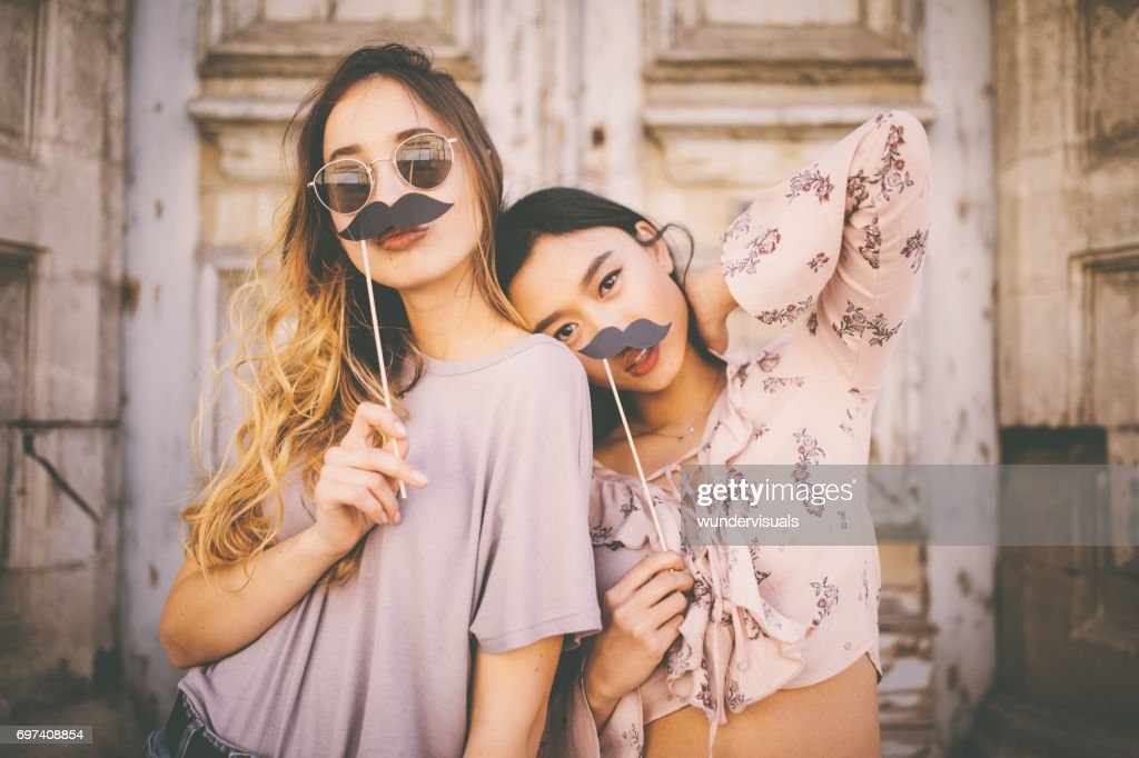 Women playing with mustaches on sticks in city streets : Stock Photo