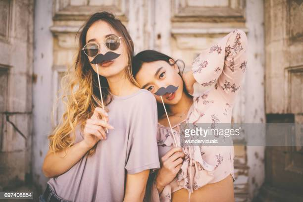 Women playing with mustaches on sticks in city streets