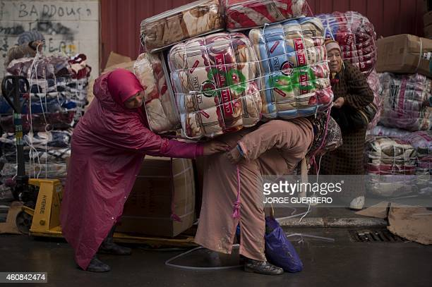 BAZINET Women porters load bundles onto their back for transport across the El Tarajal boarder separating Morocco and Spain's North African enclave...