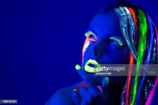 women portrait with glowing multi colored makeup in black light - fluorescerende stockfoto's en -beelden