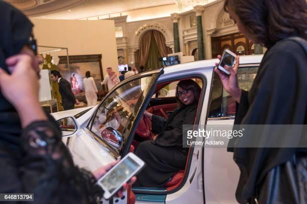Women pose behind the wheel of a car at a luxury goods fair in Riyadh Saudi Arabia on March 13 2015