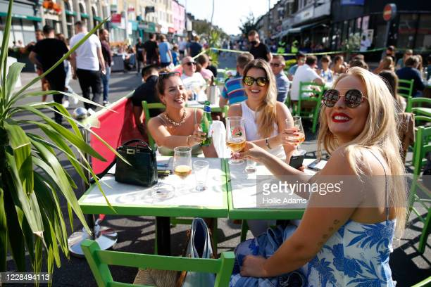Women pose for a photo at an outdoor dining area on Northcote Road in Battersea on September 13, 2020 in South West London, England. Concerned by...