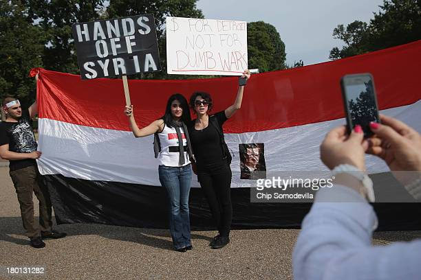Women pose for a photograh with a banner bearing the image of Syrian President Bashar alAssad during a demonstration in support of alAssad and...