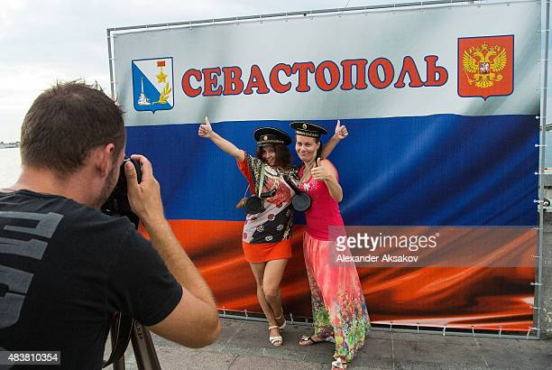 Women pose for a picture next to a Russian flag and Sevastopol print on August 12 2015 in Sevastopol Crimea Russian President Vladimir Putin signed a...