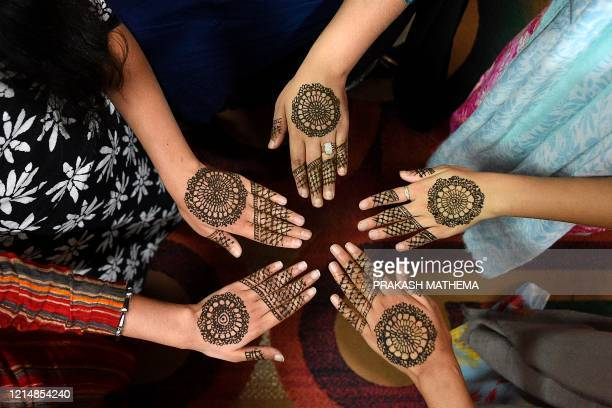 Women pose for pictures after applying hennas on the hand during 'Chand Raat' or 'Night of the Moon' in Kathmandu on May 24 on the eve of Eid alFitr...