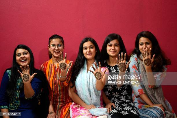 Women pose for pictures after applying hennas on their hands during 'Chand Raat' or 'Night of the Moon' in Kathmandu on May 24 on the eve of Eid...