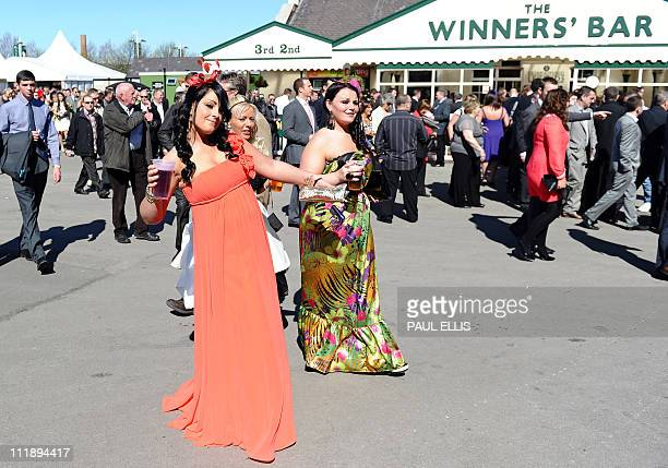 Women pose for pictures as they arrive on the second day of the Grand National meeting at Aintree Racecourse in Liverpool northwest England on April...