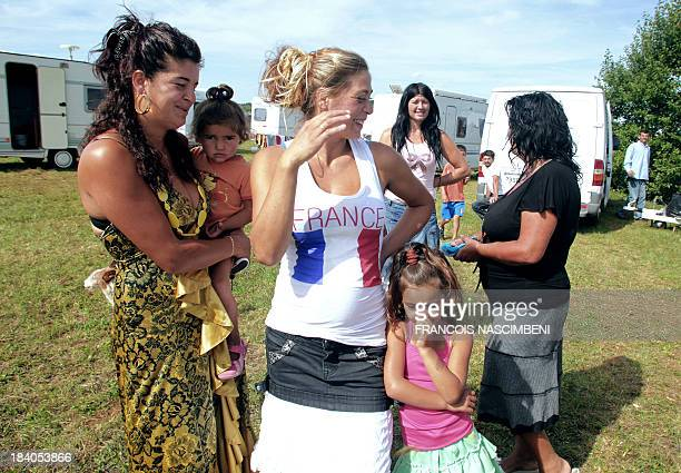 Women pose in front of caravans on August 19 2010 on an airfield where people belonging to the Roma community camp in SemoutiersMontsaon northern...