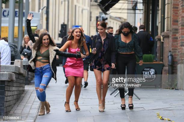 Women pose in the street on a night out in Newcastle, northern England on July 4 as restrictions are further eased during the novel coronavirus...