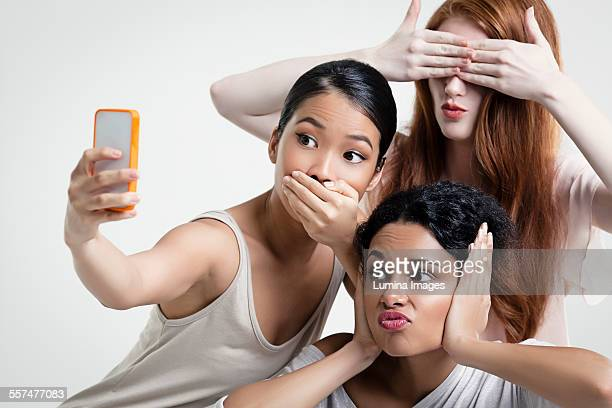 Women posing and taking cell phone selfie
