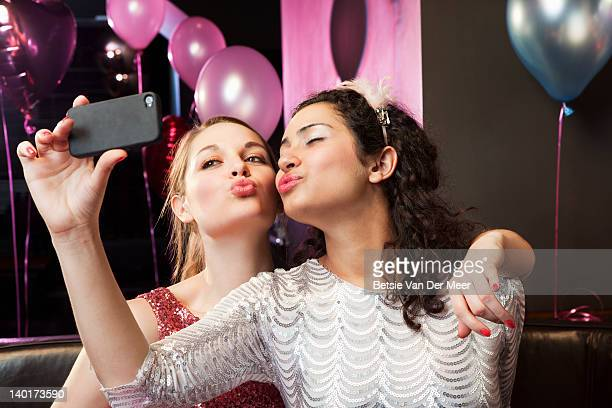 Women posing and taking photo on mobile phone.