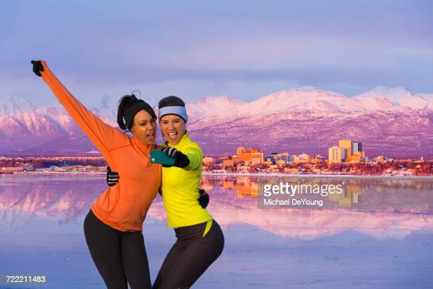 Women posing for cell phone selfie near mountain river
