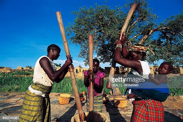 Women pounding millet in a mortar Dogon Sangha village Bandiagara Escarpment Mali