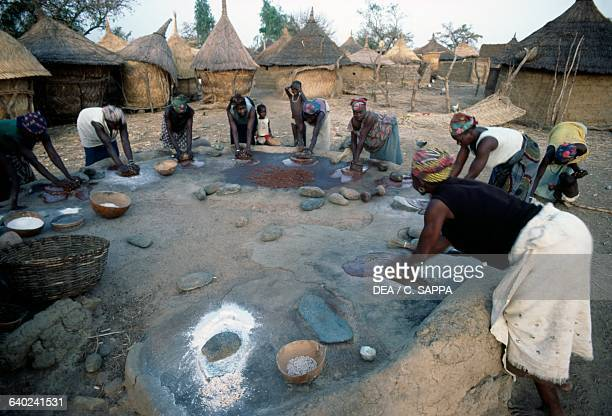 Women pounding shea nuts near the monastery in Koubri, Burkina Faso.