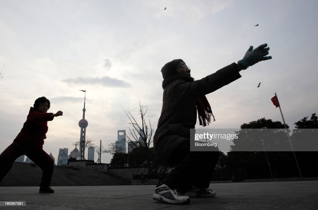 Women practice Tai Chi on the Bund as commercial buildings stand in the Pudong area, background, in Shanghai, China, on Tuesday, Jan. 29, 2013. China's economic growth accelerated for the first time in two years as government efforts to revive demand drove a rebound in industrial output, retail sales and the housing market. Photographer: Tomohiro Ohsumi/Bloomberg via Getty Images