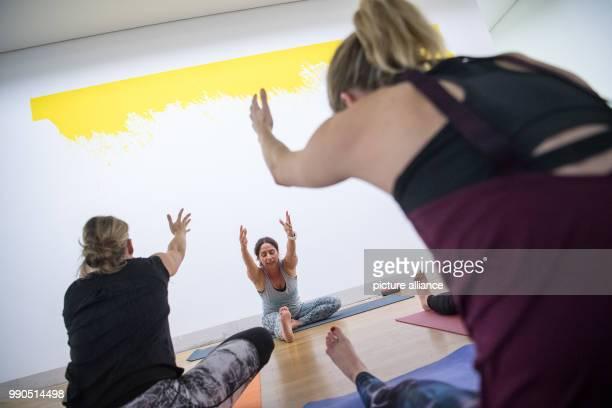 Women practice yoga during a yoga course in front of the art work Trevira of Leni Hoffman at the Gallery Stadt Sindelfingen in Sindelfingen Germany...