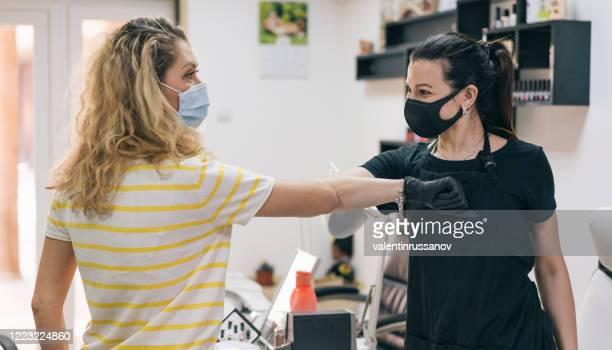 femmes pratiquant l'accueil alternatif pour la sûreté et la protection pendant covid-19 - éviter de se serrer la main photos et images de collection