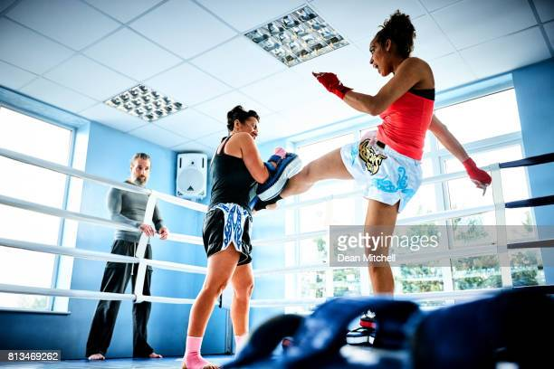Women practicing fight attack in boxing ring