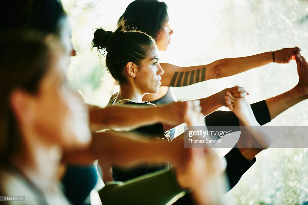 Women looking out window of studio while practicing yoga