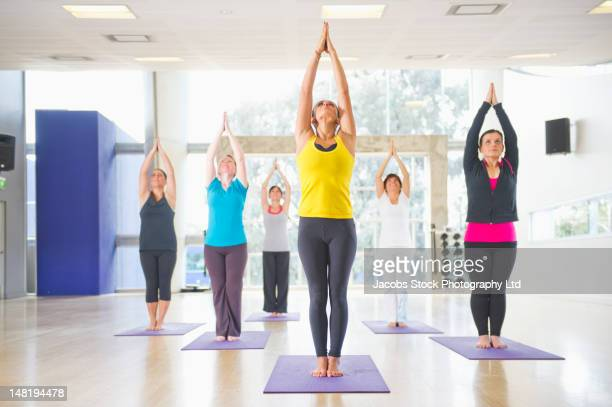 women practicing yoga in class - yoga studio stock pictures, royalty-free photos & images